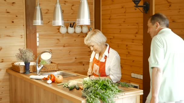 Egy régi férj veszi a felesége kést, és apróra vágott sárgarépát. Egy idős ember áll a konyhában, és apróra vágott sárgarépa gyűrűk. Feleség átölelve férjét, videó
