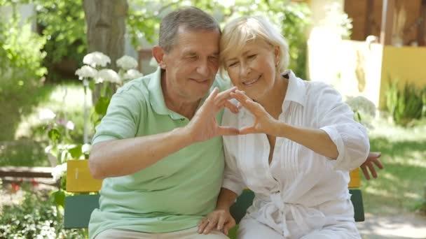 Az idősebb kezek megmutatják a szívet. Idős pár, akik egy padon ülnek egy ölelésben. Férj és nő ül a kertben és mosolyog.