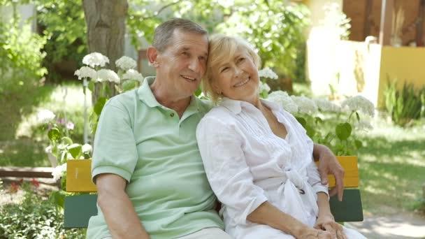 Starší pár sedí na lavičce v objetí. Muž a žena sedí na zahradě a usmívají se. Manželka říká svému manželovi, že sedí na lavičce.
