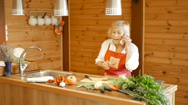 Starší žena krájí mrkev a zvedá telefon. Žena telefonovala v kuchyni a opírala se o kuchyňský stůl. Žena v bílé košili a červené zástěře..