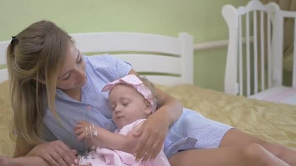 Baby spielt mit einem Haarreifen. kleines Mädchen auf dem Schoß ihrer Mutter liegend. junge Mutter mit ihrer Tochter auf dem Bett liegend. Baby in rosa Kleid und Kopfverband.