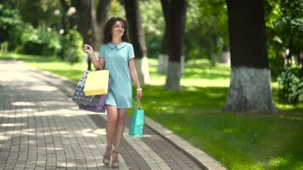 Curly žena je chůze s nákupními taškami v parku