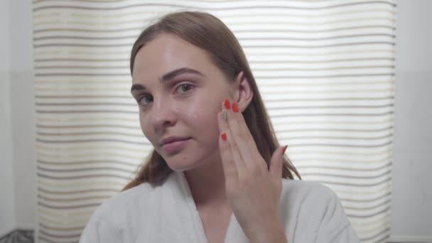 Atraktivní mladá žena s heterochromia, jak se dívá do kamery a používá denní krém na obličeji v koupelně. Péče o pokožku, koncept krásy. Série skutečných lidí.