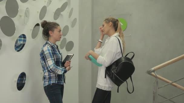 Kamera se pomalu pohybuje zprava doleva. Dvě mladé dívky stojí na chodbě a povídají si. Hezká dívka drží tablet a smartphone v rukou. Roztomilá dívka v bílé košili drží notebook v rukou.