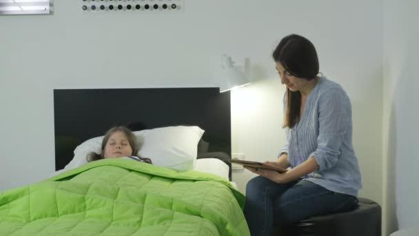 Moderní matka sedí u postele se svou dcerou a čte pohádku na dobrou noc. Holčička usne a matka se podívá, dotkne se vlasů, políbí čelo, zhasne světlo a odejde z ložnice.