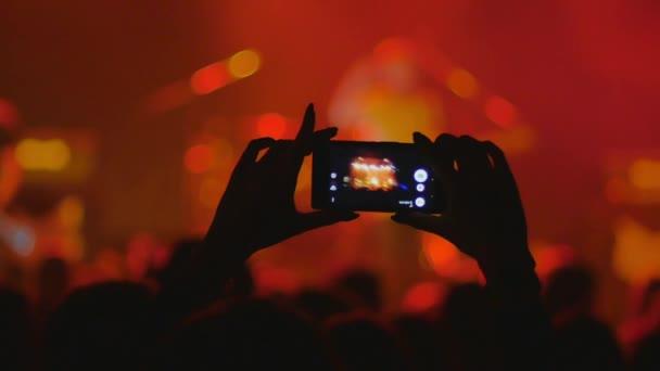 osoba z davu nahrávání show na mobilním telefonu
