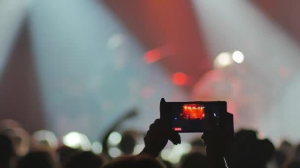 lidé se sváže, zatímco hudebníci hrají na jevišti, uživatel nahrává video na mobilním telefonu