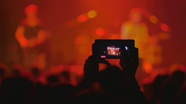 koncertní video, párty pro lidi, zatímco hudebníci hrají na jevišti, šťastní tančící dav, osoba nahrávací show na mobilním telefonu