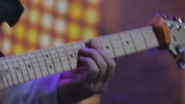 The guitarist playing on the electronic guitar on the concert. The man with guitar stands on the scene and performs a music. Musician plays guitar at the rock concert. Illumination is blinking around the rock-guitarist.