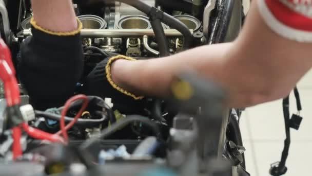 Opravářský motor motocyklu. Ten muž otáčí maticí šroubovákem. Oprava detailů uvnitř motoru motorky. Detailní záběr. Kamera se pohybuje zprava doleva.
