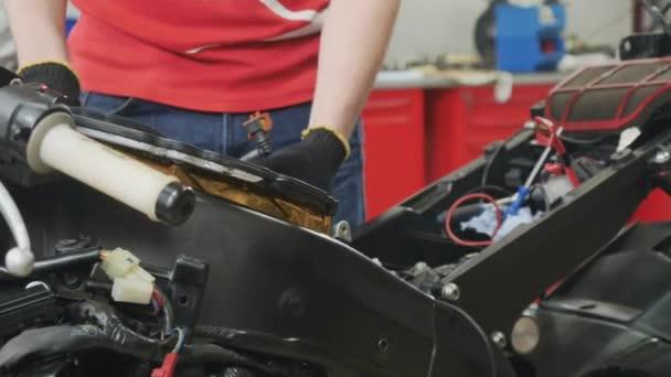 Inženýr nastavit vzduchový filtr v motocyklu. Dělník opravuje motorku. demontáž motoru moderních silničních motocyklů. Detailní záběr.