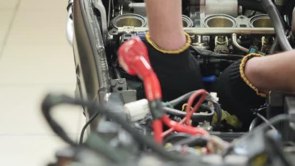 Opravářský motor motocyklu. Ten muž otáčí maticí šroubovákem. Oprava detailů uvnitř motoru motorky. Detailní záběr. Kamera se pohybuje zleva doprava.