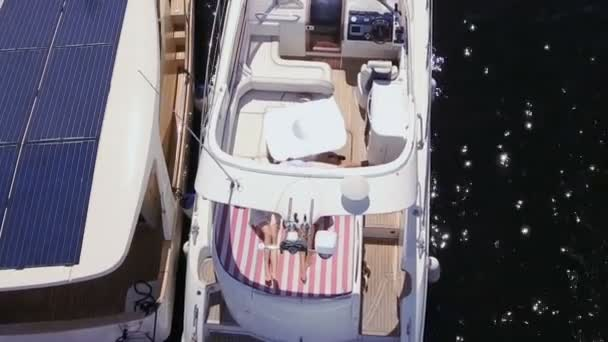 Der junge Kapitän der Jacht flirtet und unterhält sich mit zwei Frauen, die Champagner trinken. attraktive Mädchen und Männer haben Spaß mit Kapitänsmütze. Junge Leute entspannen sich und machen eine Kreuzfahrt auf Jachten. Luftaufnahmen.