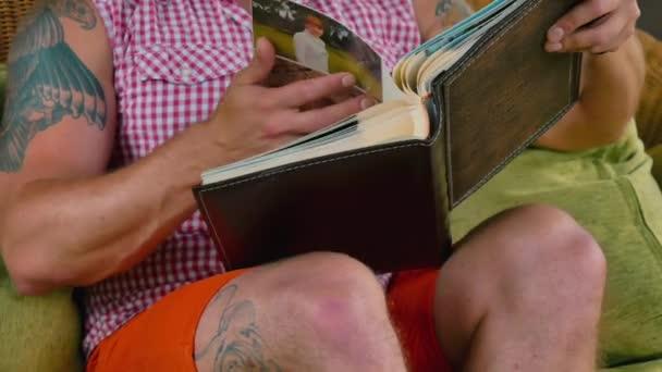 Der Mann entspannt sich zu Hause auf dem Sofa. Junger Mann mit Tätowierungen blättert im Fotoalbum und erinnert sich an einige besondere Momente aus dem Leben. junger Mann hat eine gute Zeit allein zu Hause.