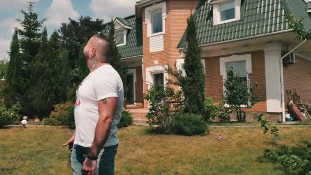 Boldog új tulajdonosa a nyaralónak. Egy fiatal fickó portréja kulcsokkal egy új vidéki házból. Az izmos ember körülnéz az új háza területén. Happy belenéz a kamerába, bemutat egy kulcsot egy házból, és felmutatja a hüvelykujját..