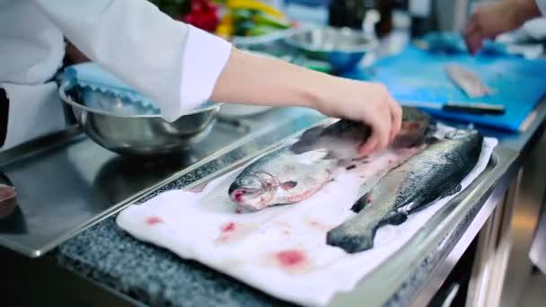 Drei rohe Fische am Handtuch auf dem Tisch. Der Koch nimmt einen der rohen Fische vom Tisch.