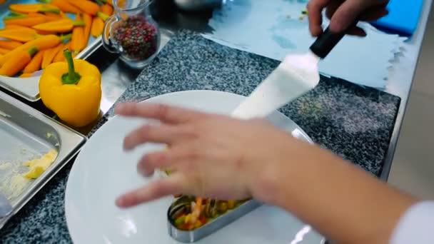 Der Koch legte den Fisch mit Zucchini auf den Teller. Der Koch dekoriert das Gericht mit Fisch und gießt die Sauce auf Teller und Teller.