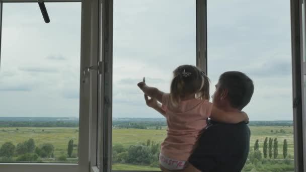 Otec drží malou dceru ve zbrani a přišel k oknu. Šťastná holčička a její táta se dívají z okna a mávají rukama. Šťastná rodina se spolu dobře baví..