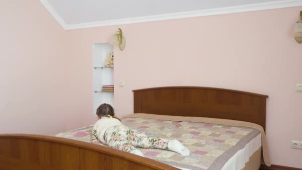 Little girl has fun at the bed at home. Cute child is relaxing and moves along the bed. Pretty girl is boring and plays with herself.