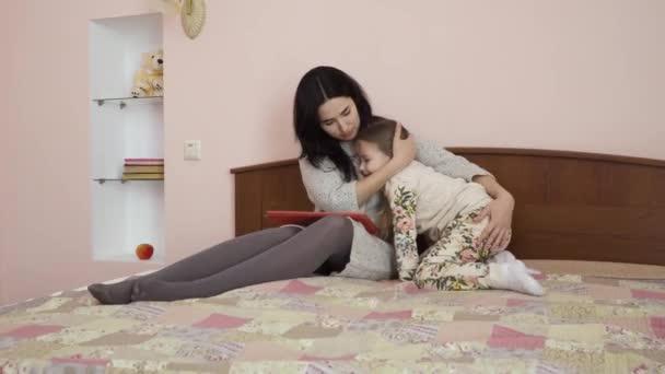 Matka a holčička se objímají doma na posteli. Hezká žena a rozkošná dívka ukazují své pocity jeden druhému. Žena drží digitální tablet na kolenou.