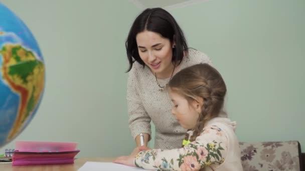 Matka pomáhá své malé dceři dělat domácí úkoly. Mladá žena ukazuje dívce, jak správně psát v sešitu. Matka tráví svůj volný čas tím, že pomáhá své dceři v první třídě se studiem. Kodek Prores.