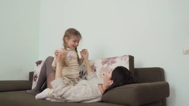 Mladá matka s roztomilou dceruškou odpočívají doma na gauči. Šťastná rodina se tu poflakuje a tráví spolu volný čas. Krásná matka a její dítě leží a na pohovce v obývacím pokoji.
