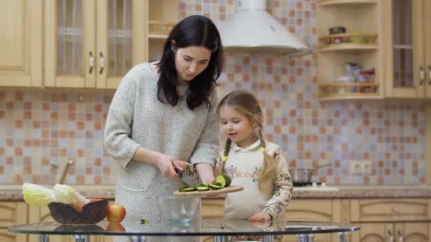 Young mother teaches her little daughter to cook at the kitchen. The family is preparing salad with fresh vegetables and put the cutted cucumber into a bowl. Young woman spend her leisure time together with little daughter at home. Prores codec.