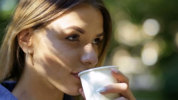 Young woman drinking coffee from disposable cup. Pretty blonde enjoy of drinking delicious beverage. Close-up. Slow motion.