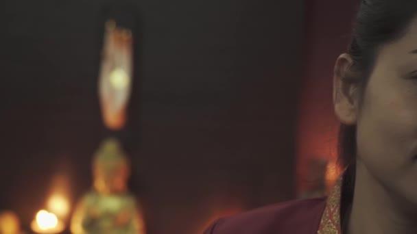Výrazné tmavé oči thajské masérky. Krásná mladá žena v červeném županu v masážním salonu. Kamera jede zleva doprava. Detailní záběr.