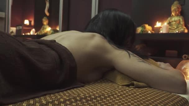 Hezká žena v thajské masážní místnosti. Pohled na krásná záda. Přesouvám kameru zprava doleva. Detailní záběr.
