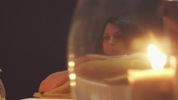 Sladká dívka v masážním salónu leží na posteli na masáž. Než se zapálí svíčky na posteli. Detailní záběr.