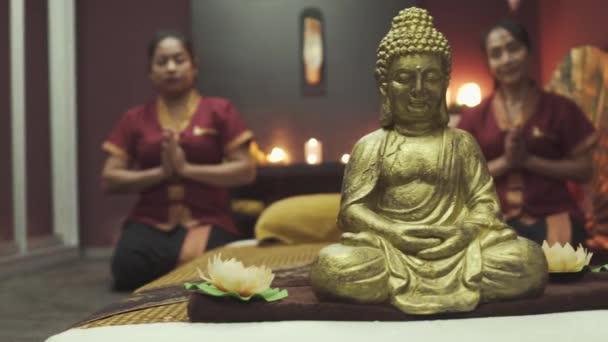Dvě krásné thajské masérky v červeném rouchu sedí v lotosové póze poblíž sochy Buddhy. Zavřít.