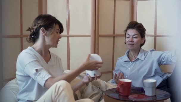 Two cute mature women sitting at the small table on comfortable pillow chairs drinking coffee and talking about cosmetics. Younger lady shows her friend a new cream. Body care. Slow motion.