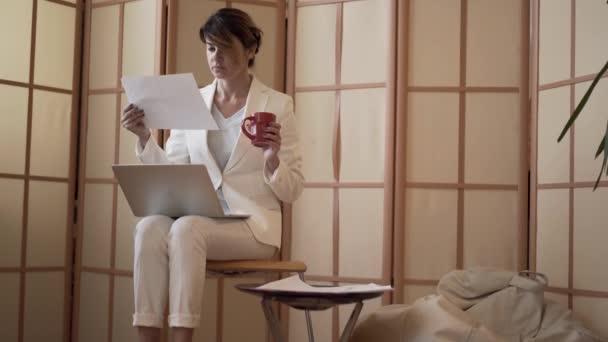 Dospělá bělošská obchodní žena v bílém formálním obleku popíjí kávu a dívá se na obrazovku přenosného počítače a na papír, který sedí doma. Žena Klečka na krku. Zpomaleně.