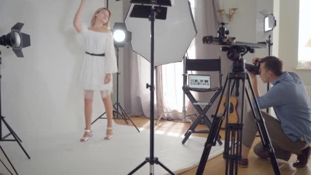 Dietro le quinte del servizio fotografico. fotografo professionista scattare foto di donna carina in posa su sfondo bianco in studio. Rivista di moda studio photoshoot.