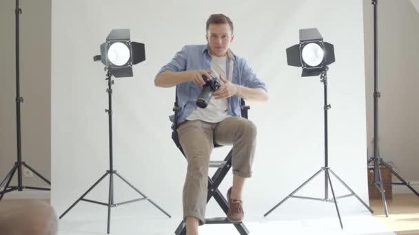 professioneller Fotograf, der Fotos macht, während er auf dem Stuhl sitzt und in die Kamera schaut. Fotograf auf weißem Hintergrund im Studio. Fotoshooting für Modezeitschrift Studio.