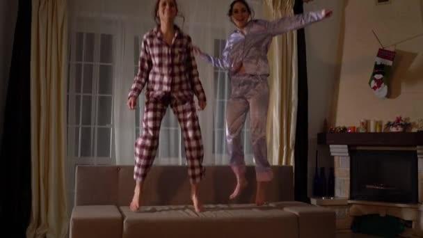 Çocukluktaki gibi rahat bir oturma odasında kanepede zıplayıp eğlenen pijamalı, yetişkin ikiz kardeşler.