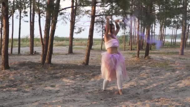 Gyönyörű lány fényes smink egy rózsaszín ruha tánc füst bombák a háttérben a fenyőfák.