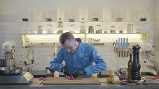 Blonďatý kuchař muž v restauraci uniformu a černé rukavice stojí v moderní kuchyni s mnoha kuchyňské nádobí kolem a řezání plátky tuňáka.