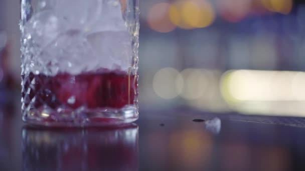 Barman dává další kostky ledu do sklenice s koktejlem pro návštěvníka v moderním nočním klubu zblízka. Noční životní styl
