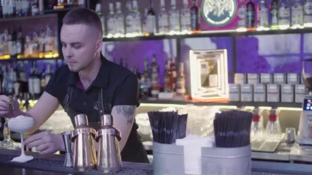 Csapos a bárban keveredik hosszú kanál jégkockákkal a pohárban. Buli van. Étteremtervezés. A sok üveg alkoholra a polcokon..