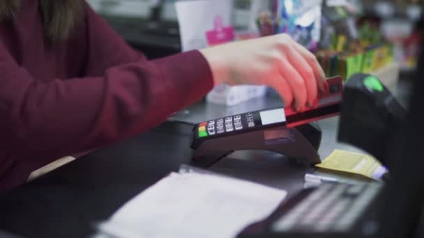 Female hand is holding a credit card over the terminal. Payment by card through the POS terminal.