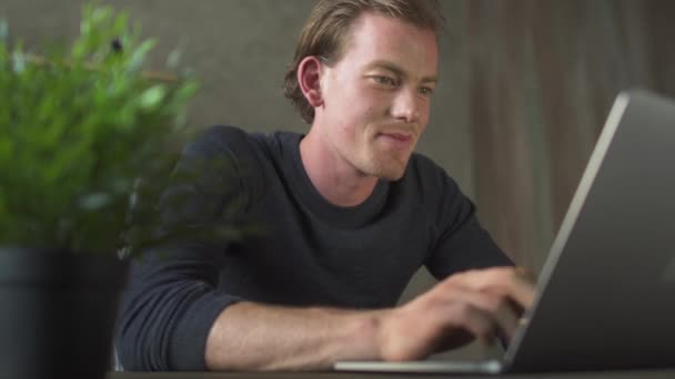 Smiling young blond man sitting at computer and typing at laptop messages thinking about topic.