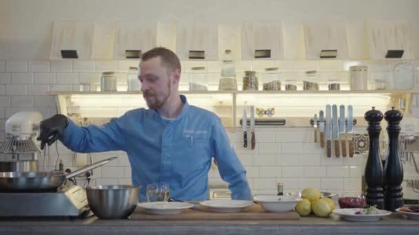 Profesionální kuchař vařič v černých rukavicích friyng nebo dušené plátky cukety a kukuřice na pánvi s olejem. Detailní záběr.