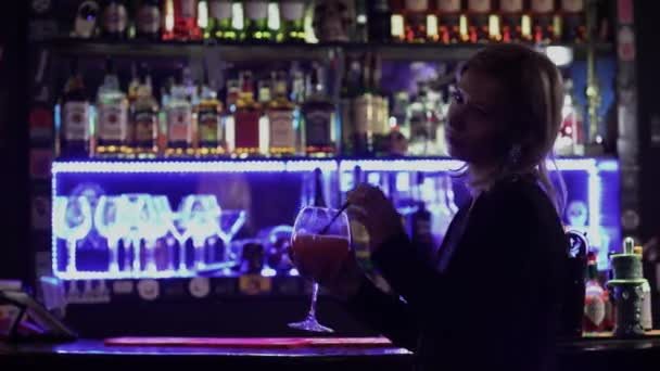 Beautiful girl with blond hair standing near the bar counter on the background of flickering light in a nightclub. Cute woman is resting and drinking a delicious cocktail alone.