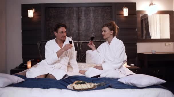 Krásný pár pije alkohol sedí v posteli v moderním hotelovém pokoji. Milenci v županech odpočívají na pohodlném místě
