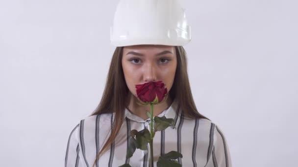 Mladá krásná žena ve stavebnictví bílý klobouk drží červenou růži v rukou a šťastně voní květiny