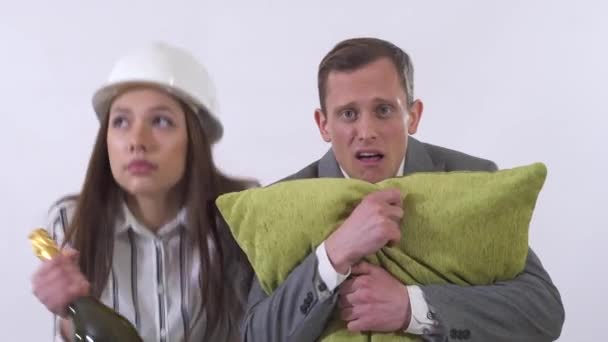 Potrait of crazy couple close up. Man holds pillow, woman in builders helmet dancing with champagne bottle. Man looks on lady puzzled, trying to hide behind a pillow. Shooting in the studio on a white background