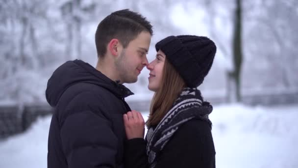 Beautiful young woman in winter park under falling snow, video