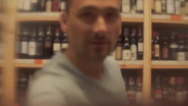 Portrét muže, který pije červené víno zblízka. Muž přiloží sklenici velmi blízko ke kameře a pak ochutná alkoholický nápoj. Veselý pes s vousy vypadá ve fotoaparátu